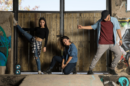 Three young Hispanic dancers showing some of their dance moves in an abandoned building Фото со стока