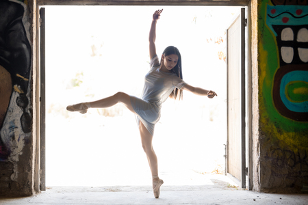 Gorgeous young ballet dancer standing en pointe and performing a dance routine in an urban setting Stock Photo