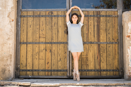 barndoor: Gorgeous ballet dancer tiptoeing on pointe shoes while performing outdoors Stock Photo