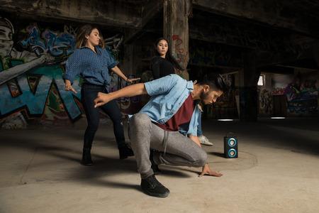 落書きの壁の前に女性のペアで踊るハンサムな若い男
