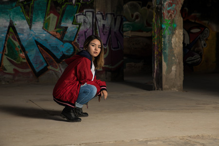 Pretty young Hispanic female dancer crouching in an abandoned building and getting ready to dance Stock Photo