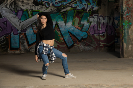 Attractive young female urban dancer practicing some dance moves in an abandoned building