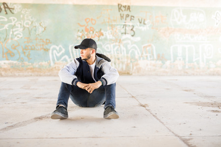 Good looking male urban dancer sitting outdoors in an urban setting with graffiti walls. Lots of copy space
