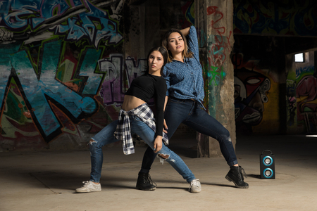 Full length view of a couple of female urban dancers performing and freestyling with some music