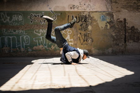 Full length view of a young male dancer practicing some breakdancing moves in an abandoned building Stock Photo