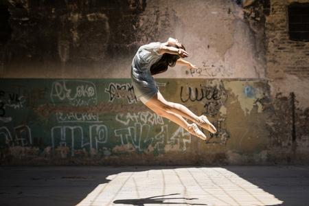 Dramatisch portret van een mooie vrouwelijke balletdanser die buiten springt in een stedelijke omgeving