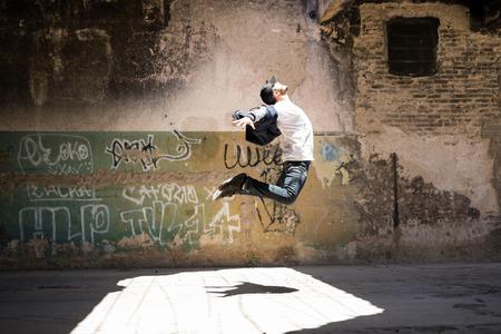 Profielmening van een mannelijke stedelijke danser die sommige dansbewegingen uitoefenen en in openlucht springen