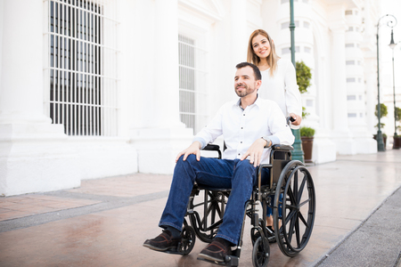 Cute young woman going for a walk with his boyfriend in a wheelchair while having a good time together