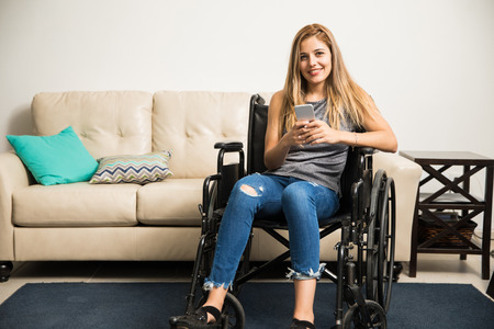 Portrait of a beautiful young woman on a wheelchair using a smartphone and relaxing at home