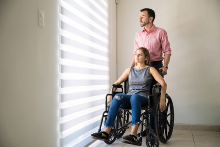 Full length portrait of a sad young woman sitting on a wheelchair with her husband at home Stock Photo