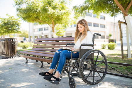 Full length view of a pretty young woman on a wheelchair relaxing and reading a book outdoors