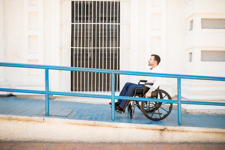 Profile view of a good looking young man going up a building ramp on a wheelchair Stock Photo