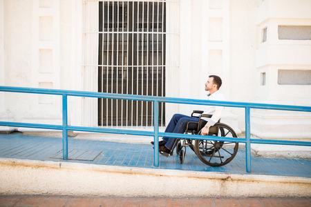 Profili il punto di vista di un giovane bello che va su una rampa della costruzione su una sedia a rotelle Archivio Fotografico - 82479261