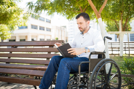 Good looking young Hispanic man in a wheelchair reading a book while passing time in a park
