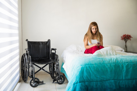 Sad young woman sitting in bed next to a wheelchair and using her smartphone