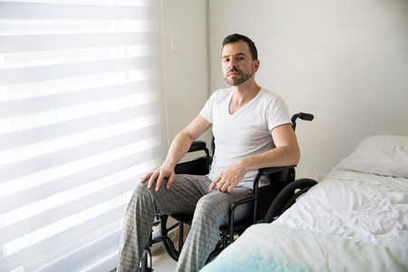 Attractive young Latin on a wheelchair looking serious and sad while sitting in his bedroom at home