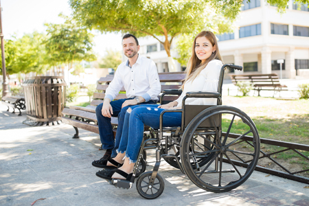 Portrait of a beautiful young woman in a wheelchair meeting a guy for a date at a park and smiling