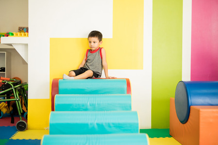Portrait of a little boy taking a break from an obstacle course in a physical therapy center