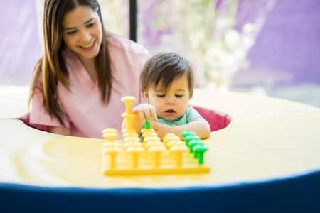 Female therapist and a baby practicing stacking and playing together in a school Stock Photo