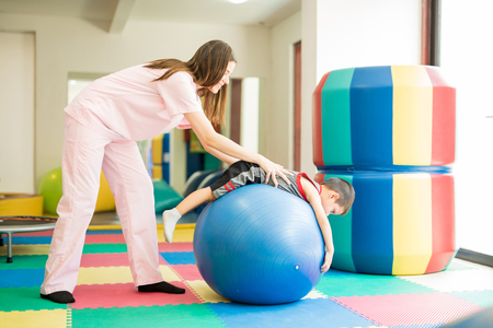 Profile view of a therapist helping an autistic young boy calm down while lying on top of a stability ball in a therapy center