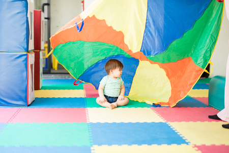 Baby girl looking at a parachute and exploring different colors in an early stimulation center Stock Photo