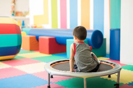 トランポリンの上に座って、子供のリハビリ センターで障害物コースから休憩を取って小さな男の子の背面図