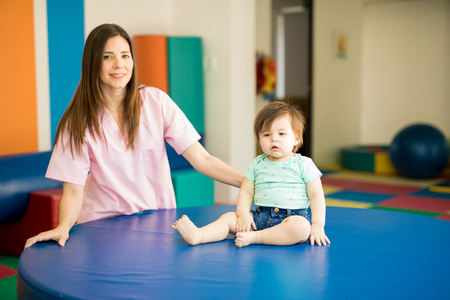 Pretty Latin baby working on her balance in an early stimulation school with the help of her therapist