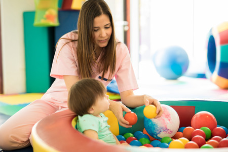 Attractive female therapist playing with a baby in a ball pool in a children therapy center Stock Photo