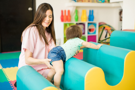 Baby and her therapist working on some crawling and climbing exercises in a therapy and stimulation center Stock Photo