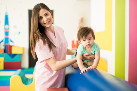 Portrait of a gorgeous Hispanic therapist doing some early stimulation exercises with a baby Stock Photo - 83467203