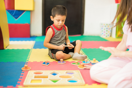 Portrait of a good looking Latin toddler playing and discovering different shapes in a therapy and learning center Stock Photo