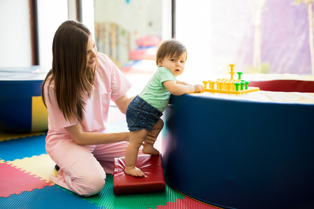 Portrait of a Hispanic baby standing and practicing maintaining balance while playing in a children therapy center Imagens