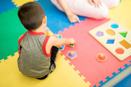 Top view of a young boy playing and learning different shapes in a therapy and education center