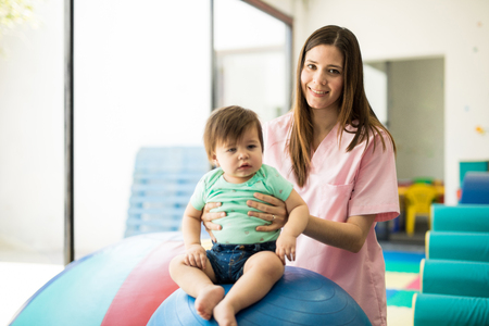 Portrait of a gorgeous Hispanic children therapist doing some early stimulation with a baby girl on a stability ball Stock Photo