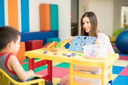 Retrato de un terapeuta de lengua femenina hermosa trabajando y practicando el alfabeto con un niño Foto de archivo - 84332433