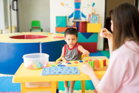 Kleine jongen krijgt taalterapie en leer het alfabet in een revalidatie- en kinderontwikkelingscentrum