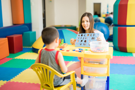 Good looking female language therapist working with a boy in a rehabilitation center 스톡 콘텐츠