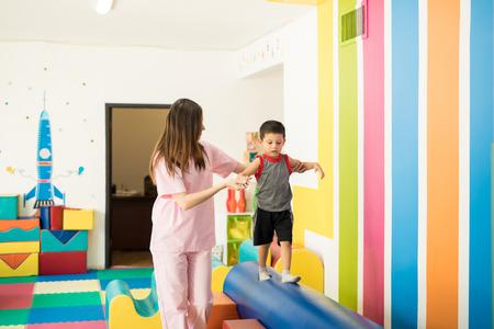 女性セラピスト療法センターでビームに歩きながらバランスを維持するために子供を助けること