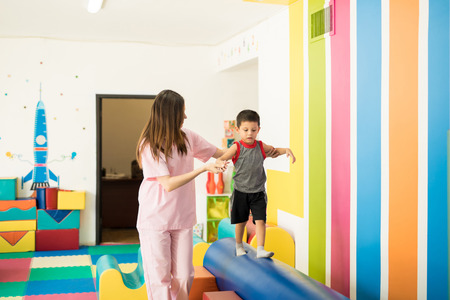 Female therapist helping a kid to maintain balance while walking on a beam in a therapy center Stockfoto