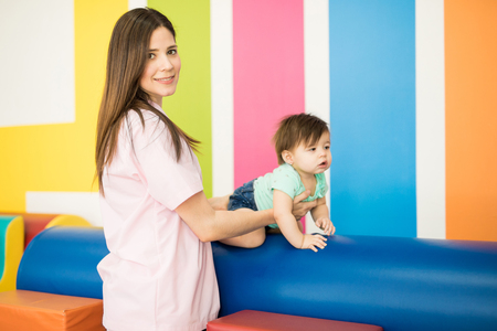 Pretty young woman working as a therapist with a baby in a child therapy and development center Stock Photo