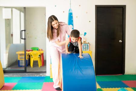 Spaanse jongen die kruipt en gaat en hinderniscursus met de hulp van een therapeut in een fysieke therapieschool Stockfoto