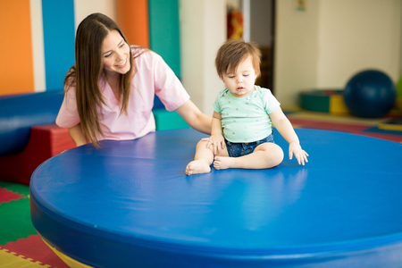 Cute female therapist helping a baby practice balance on an early stimulation and development school