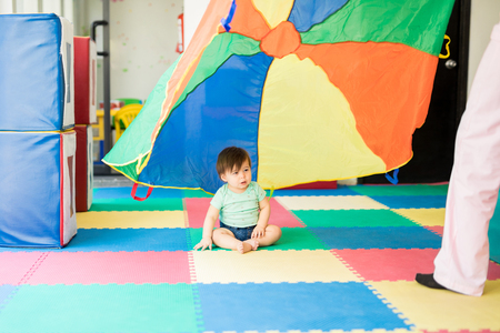 Pretty baby looking at a colorful parachute in an early stimulation class Stock Photo