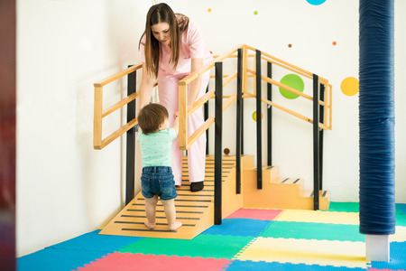 Children therapist helping a baby walk up a ramp as part of their early stimulation exercises at a school