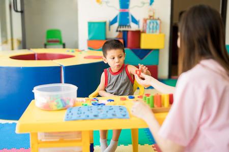 Niño pequeño aprendiendo el alfabeto con un terapeuta de lenguaje en una clase de educación especial Foto de archivo - 84332459