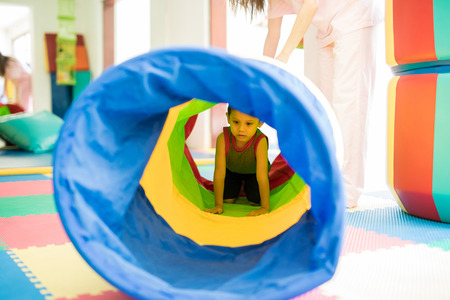 Little kid playing and crawling through a tunnel in an obstacle course at a children physical therapy center