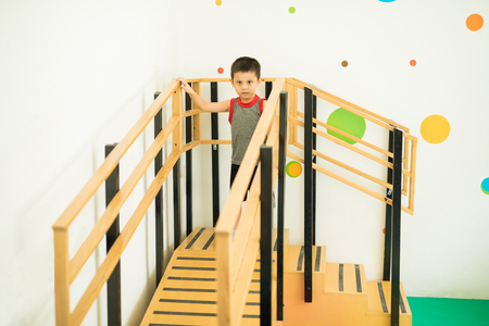 bajando escaleras: Portrait of a little boy walking up the stairs and going down on a ramp as part of his physical therapy Foto de archivo