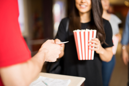 Closeup of a woman holding a bag of popcorn and handing her ticket at the movie theater entrance