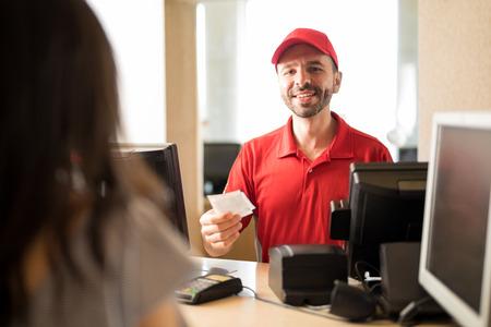 Portrait d'un beau travailleur hispanique vendant des billets à un client au cinéma