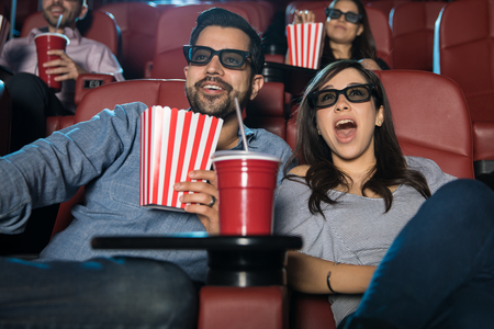 Portrait of a cute couple with 3d glasses watching a movie in the cinema theater and looking suprised Foto de archivo